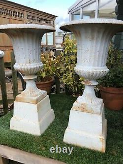 PAIR of rusty white campagna urns & plinths cast iron urns