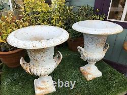 Pair of cast iron urns with raised motif and handles cast iron urns